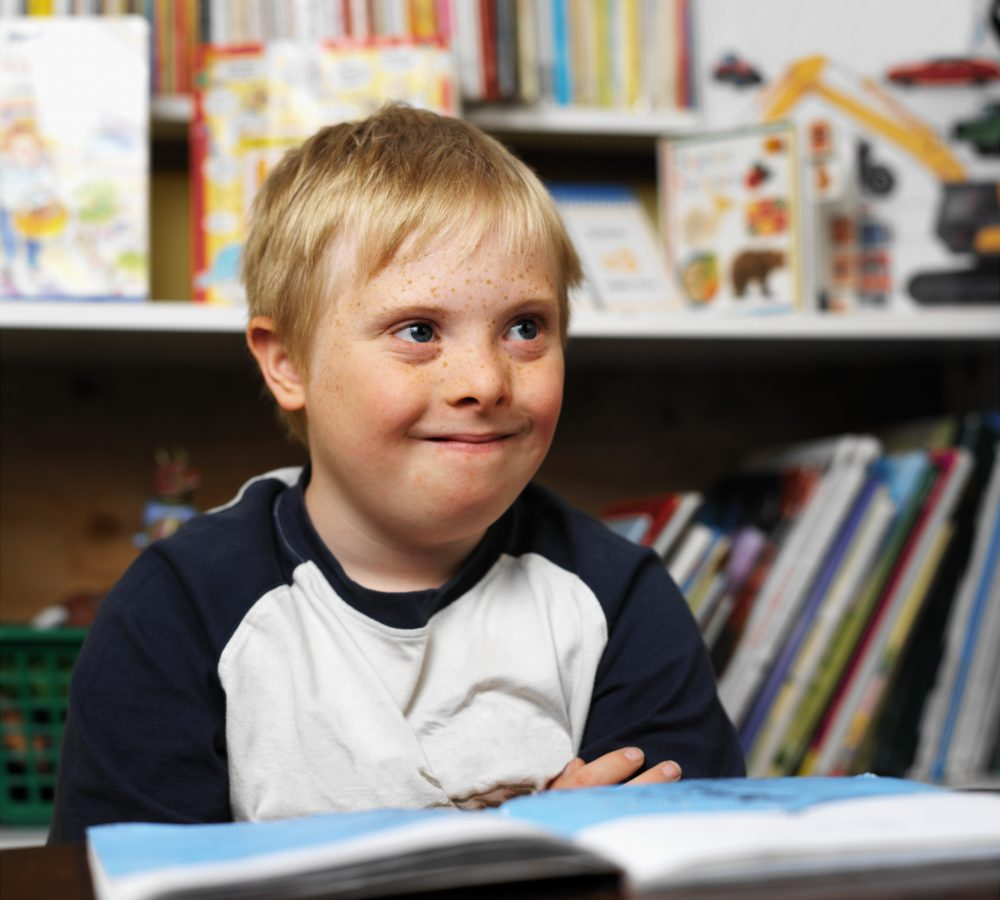 boy (7-10) with down syndrome in a classroom